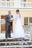 Young wedding Caucasian Russian couple standing in front of the building in winter — Stock Photo