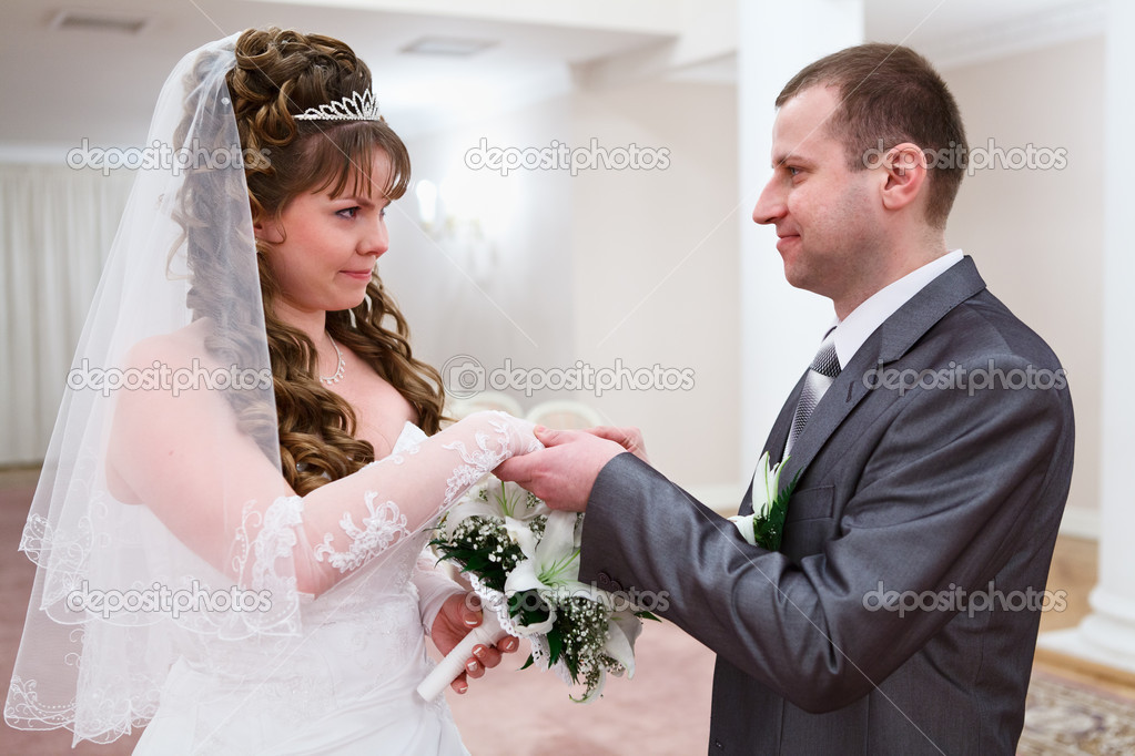 Bridegroom puts a wedding ring on brides finger — Stock Photo #10950102