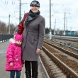 Mother and small daughter standing on railway station platform — Stock Photo #11347470