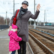 Mother and small daughter standing on railway station platform — Stock Photo #11347472