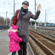 Royalty-Free Stock Photo: Mother and small daughter standing on railway station platform