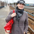 Stock Photo: Portrait of happy fashion young Caucasiwomin coat and cap with red bag