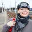 Portrait of happy smiling woman in cap standing on railway station — Stock Photo