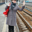 Woman in coat and cap wave goodbye standing on train station - Stock Photo