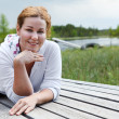 Happy smiling woman laying on wooden boards on river edge. Copyspace — ストック写真