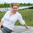 Happy smiling woman sitting on wooden boards on river edge. Copyspace — ストック写真