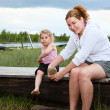 Mother helping small daughter to wear boots on river — Stock fotografie