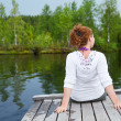 Young woman turning back sitting on wooden boards on pond edge — Foto Stock