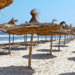 Mediterranean stormy sea coast and empty sandy beach with parasols — Foto Stock