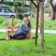 Young woman sitting on the garden swing along and smile — Foto de Stock