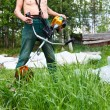 Unrecognizable lawn-mower with chopper trimer mowing grass. Focus on trimer — Stock Photo