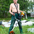 Mature Caucasian man a lawn-mower with chopper trimer mowing grass. — Stock Photo