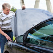 Mature man opens car hood to repair breakdown in his car — Stock Photo