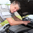 Mature Caucasian man checking a oil level under car engine jacket — Stock Photo