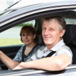 Mature happy Caucasian couple sitting in domestic car and smiling — Stock Photo
