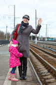Moeder en kleine dochter permanent op railway station platform — Stockfoto