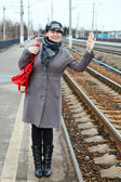 Woman in coat and cap wave goodbye standing on train station — Foto Stock