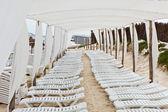 Blancos plásticos tumbonas en la playa bajo una sombrilla grande — Foto de Stock