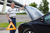 Mature man holding emergency triangle and opened car hood — Stock Photo