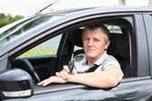 Kontak anahtar araba sürücü koltuğu ve gülümseyerek oturan ile kıdemli mutlu erkek — Stok fotoğraf