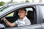 Mature man sitting in car on driver seat and holding steering wheel — Stock Photo