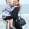 Happy mother and little daughter together Small child on womans hands. Caucasian standing on sea coast — Stock Photo #12199966