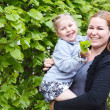 Happy mother and little daughter together Small child on womans hands. Copy space. Green leaf as background — Stock Photo
