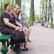 Three women different ages are sitting on bench in park. Grandmother, mother and small daughter — Stockfoto