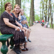 Three women different ages are sitting on bench in park. Grandmother, mother and small daughter — Stok fotoğraf