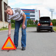 Mature man sets triangle warning sign on road and going to car with blinker lights on wayside — Stock Photo