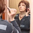 Stock Photo: Mature Caucasiwomapplying make-up against mirror in domestic room