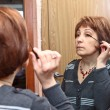Mature Caucasian woman applying make up against mirror in domestic room — Stock Photo