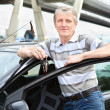 Happy mature driver with car key standing near own land vehicle — Stock Photo