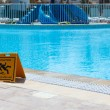 Stock Photo: Sign slippery floor by pool