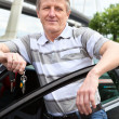 Stock Photo: Mature driver with ignition key standing near the car