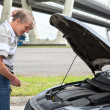 Stock Photo: Confused mature driver standing in front of vehicle with opened engine compartment hood