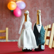 Stock Photo: Two bottles of champagne wearing like a bride and groom standing on table.