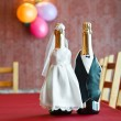 Two bottles of champagne wearing like a bride and groom standing on table. - Foto de Stock