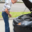 Confused mature driver standing in front of car with opened engine compartment hood — Stock Photo #12200083
