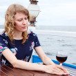Pensive woman in dress with wine glass sitting at the table — Stock Photo