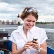 Royalty-Free Stock Photo: Happy woman at ship cafe writing a message on mobile phone