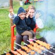 Mother and small  4 ears old daughter making faces during cooking meat — Stok fotoğraf
