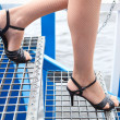 Female legs in fishnet tights and shoes in high heels going on stairs — Stock Photo