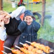 Mother and little daughter making faces during cooking meat — Stock Photo
