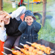 Mother and little daughter making faces during cooking meat — Stok fotoğraf