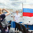 Woman photographing with Russian flag on ship deck — Stock Photo
