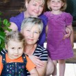 Three generation female family with four on house porch — ストック写真