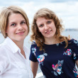 Group portrait of two smiling beautiful women standing together on vessel deck — Stock Photo