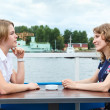 Two women talking each other at cafe table outdoors — Stock Photo