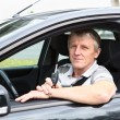 Happy senior male with ignition key sitting in car on driver seat and smiling — Stock Photo #12200244